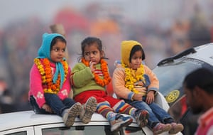 Cold weather in India: Children watch a religious procession while wrapped in woollen clothes