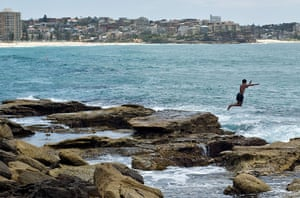 Australia heatwave: A man jumps into the sea to cool off at Manly beach in Sydney