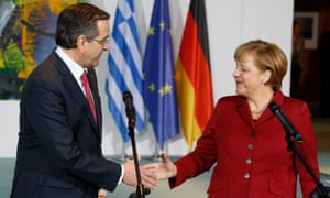 Greek prime minister Antonis Samaras (left) reaches out his hand to German chancellor Angela Merkel after they address the media at the Chancellery in Berlin 8 January  2013.
