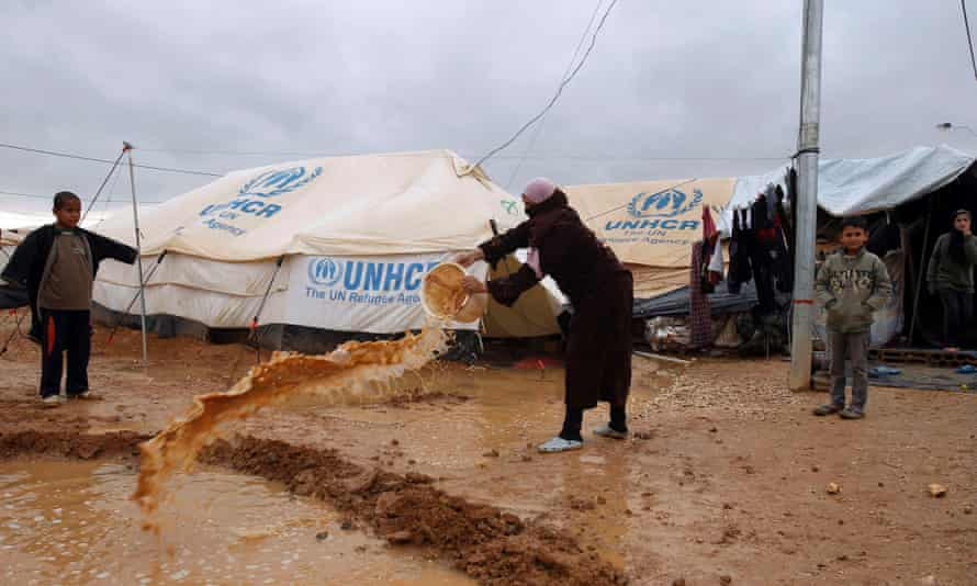 Syrian refugees shovel away water which had collected outside their tents after heavy rain at the Al-Zaatari refugee camp in the Jordanian city of Mafraq, near the border with Syria on Tuesday.