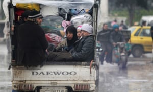 Civilians fleeing from the violence are pictured with their belongings on a vehicle in Aleppo.