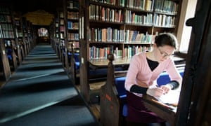 A student working in the library at Corpus Christi College at Oxford University UK