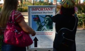 Tourists look at a sign announcing that the Statue of Liberty is closed due to a US government shutdown in New York.