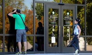 Tourists look into the closed Smithsonian National Air and Space Museum in Washington, DC, a victim of the federal government shutdown.
