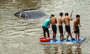 Men use a door plank to travel along a waterlogged road in Yuyao, China. The continuous rainfall brought by Typhoon Fitow has caused flooding.