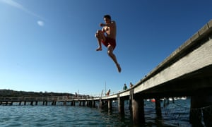 Fun in the sun: a man jumps into the water at Balmoral Beach in Sydney, Australia, as temperatures are expected to peak at 39 degrees celsius.