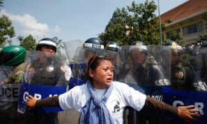 A woman reacts as police officers block the march along a street on the occasion of World Habitat Day in central Phnom Penh, Cambodia. Residents gathered to stop the government from evicting them from their homes.