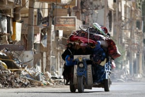 Residents travel with their belongings past damaged buildings in Deir al-Zor in Syria.