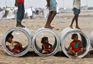 Children sitting inside cement water pipes play on the Marina beach in the southern Indian city of Chennai, India.