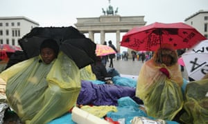 Refugees from Congo and Ethiopia huddle under rain on the second day of a hunger strike in front of the Brandenburg Gate in Berlin, Germany. Approximately a dozen refugees, some of whom have been in Germany for as long as seven years waiting for their asylum applications to be processed, claim they will continue with their hunger strike until the German government makes a firm commitment to helping them.