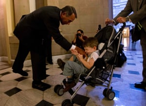U.S. House Speaker John Boehner (R-OH) (L) tickles John Griffin III, son of U.S. Representative Tim Griffin (R-AR) (not seen), after a house vote on border safety and security in Washington, October 10, 2013.