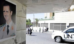 A poster of Assad in Damascus as a UN vehicle carrying OPCW inspectors passes