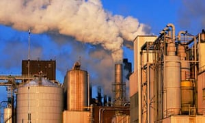 A factory emits smoke and steam on a cold winter day