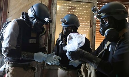 UN chemical weapons experts handle samples from the site of an alleged attack in Damascus.