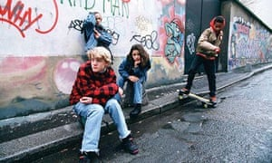 Youths on the street one with skateboard sitting in front of graffiti'd wall