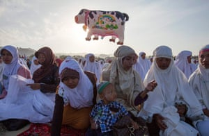Eid al-Adha: A cow balloon flies as women and children attend an Eid al-Adha mass prayer
