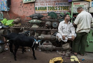 Eid al-Adha: Car parts workers talk near the goats they bought for Eid celebrations in N