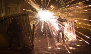 A burst of fireworks go off near members of the Black Bloc anarchist group during clashes with police after a march of striking teachers took place to mark National Teachers Day, in Rio de Janeiro, Brazil.