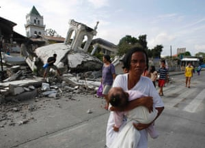 A woman carries her baby past a destroyed church belfry in Tubigon, Bohol, a day after an earthquake hit central Philippines.