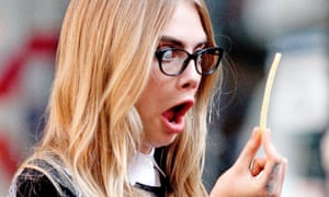 Cara Delevingne looks shocked at a chip while on a DKNY photoshoot in New York, US.