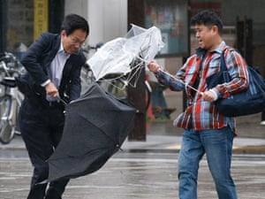 Men battle with their umbrellas against strong winds and rain caused by approaching Typhoon Wipha in Tokyo, Japan.