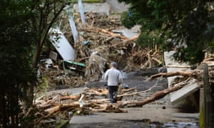 A man walks near collapsed houses following a landslide caused by Typhoon Wipha on Izu Oshima island, south of Tokyo, October 16, 2013.
