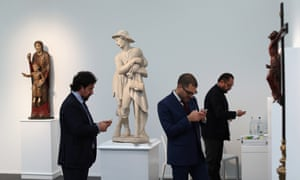 Art dealers from the Bacarelli Botticelli gallery wait in their exhibition space in the Frieze Masters Art Fair in London, England. The annual Frieze Art Fair takes place in London's Regent's Park and runs from October 17 to 20.