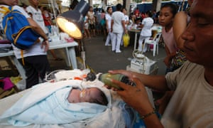 A man pumps oxygen to his newly-born son who was earlier revived by medical workers, after hospital patients were evacuated follow an earthquake in Cebu City, central Philippines.