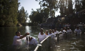 Christian pilgrims take part in a group baptism in the waters of the Jordan Riveron at the Yardenit Baptismal Site near Tiberias in northern Israel. An estimated 100,000 Christian worshippers make their pilgrimage to the Holy Land each year and one of their most sacred rituals is being immersed in the river where, according to Christian beliefs, Jesus Christ was baptised by John the Baptist.