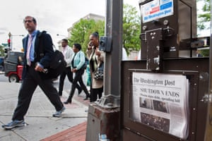 People pass a Washington Post newspaper box as they head to work near Pennsylvania Ave., NW, in Washington, Thursday, Oct. 17, 2013.
