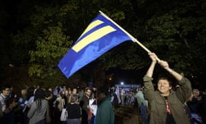 A man waves an equality flag after a marriage equality rally in Montclair