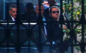 People of Freedom party (PDL) leader Silvio Berlusconi carries his pet dog as he alights from a car upon arriving at his residence in Rome in this still image taken from video September 30, 2013.