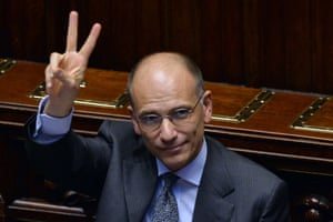 Italys' Prime Minister Enrico Letta shows the 'V-sign' for victory after his speech at the lower house of Parliament on October 2, 2013 in Rome.