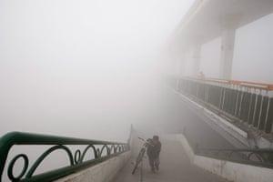 China smog: Cyclist walks to bridge