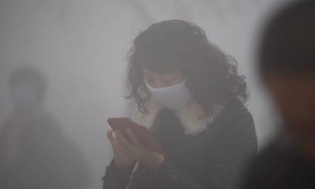 A woman wearing a mask uses her mobile phone in the smog in Harbin.