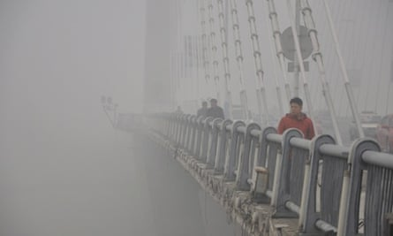 A pedestrian is picked out of gloom in his red jacket on a smoggy day in Jilin in China. Concern is growing over air quality in Chinese cities as the density of airborne particles is several times above World Health Organisation recommended limits.
