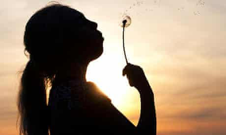 Girl blowing dandelion seed head at sunset