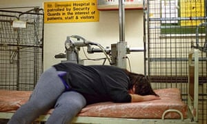 Woman on bed in hospital corridor