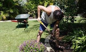 Man shovelling in garden