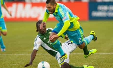 Seattle Sounders' Clint Dempsey is tackled by Portland Timbers' Diego Chara