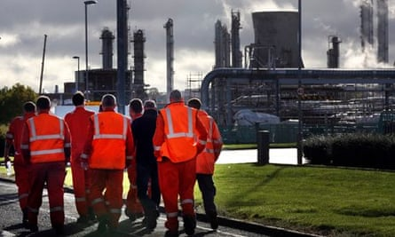 Workers walk through the Grangemouth oil refinery