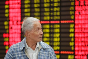 An investor looks at the stock price monitor at a private securities company in Shanghai, China Wednesday, Oct. 23, 2013.