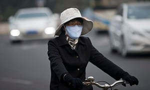 A woman wearing a face mask cycles in Beijing