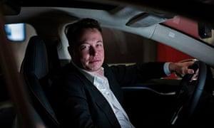 Elon Musk sits in an electric Tesla car