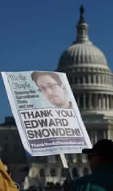 Demonstrators hold placards supporting Edward Snowden