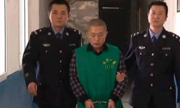 Chen Yongzhou is escorted by police officers at the Changsha public security bureau detention centre.