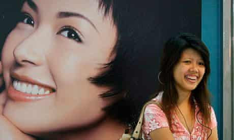 A shopper in Bangkok, Thailand, next to an advert for a skin-lightening product