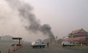 Police cars block roads leading into Tiananmen Square as smoke rises into the air