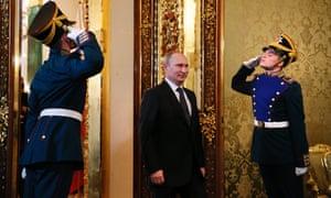 Ceremonial Kremlin guards salute as Russian President Vladimir Putin enters the room ahead of his meeting with Ecuadoran President Rafael Correa in Moscow.