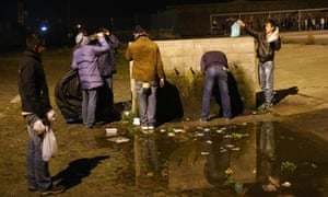 Migrants fill water bottles after eating their meal provided by volunteers working for the charity 'SALAM' in Calais, France.